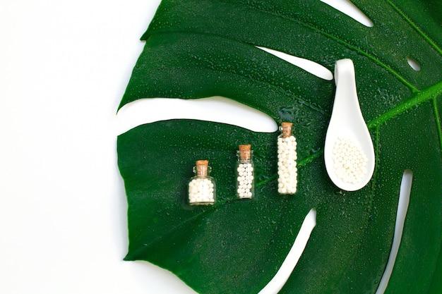 Homeopathische bolletjes in drie glazen flessen op natte palmbladachtergrond.
