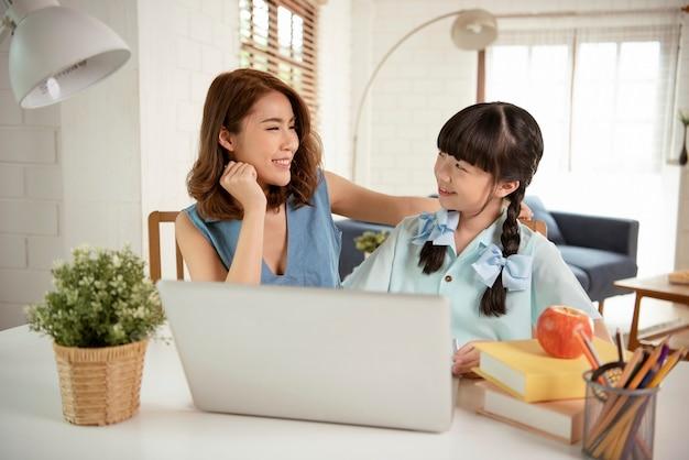 Homeschool aziatisch jong meisje student leren zittend op tafel werken met zijn tutor thuis.