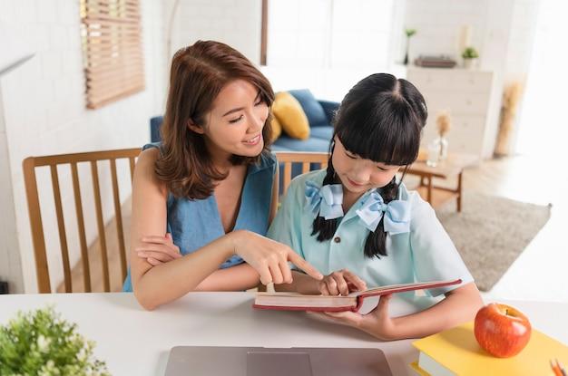 Homeschool aziatisch klein jong meisje student leren zittend op tafel werken met zijn moeder thuis.
