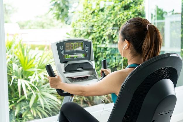 Hometrainer cardiotraining bij fitness gym van vrouw die gewichtsverlies met aërobe machine voor slank en stevig gezond in de ochtend.
