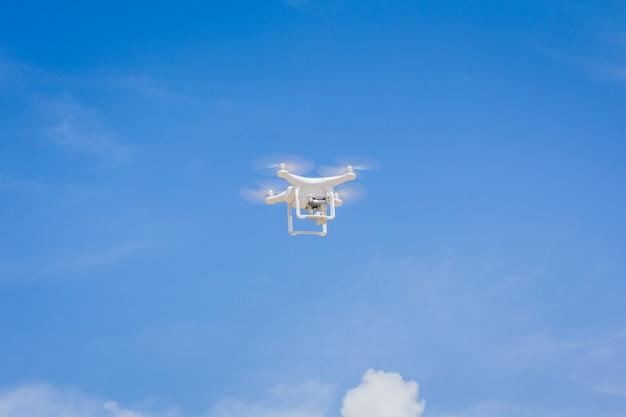 Hommel met camera die op de blauwe hemel en wolkenachtergrond vliegt