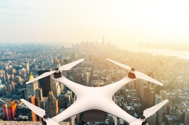 Hommel met digitale camera die over een moderne stad bij zonsondergang vliegt
