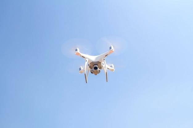 Hommelcopter die met digitale camera op de hemel en het zonlicht vliegen