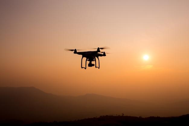Hommelsilhouet die in zonsonderganglandschap vliegen met digitale camera bij zonsondergang klaar te vliegen.
