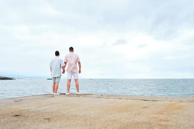 Homo mannelijk stel hand in hand met uitzicht op zee