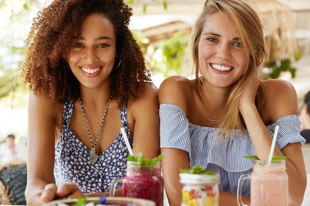 Homo-vrouwelijk koppel heeft positieve uitdrukkingen, zit dicht bij elkaar in de cafetaria, glimlacht vreugdevol, geniet van smakelijke desserts op het terras. multi-etnische lesbiennes praten met elkaar. liefde concept