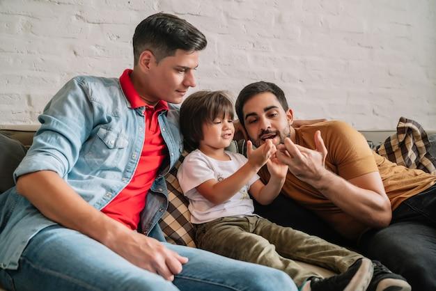 Homopaar dat plezier heeft met hun zoon terwijl ze samen tijd doorbrengen op een bank thuis. familieconcept.