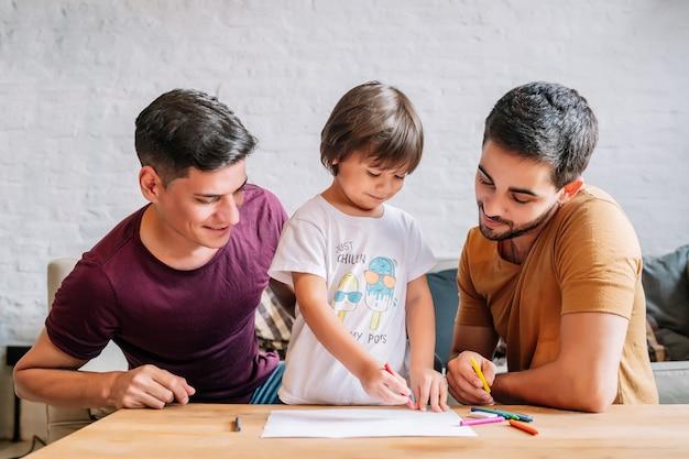 Homopaar dat plezier heeft met hun zoon terwijl ze thuis iets op papier tekenen. familieconcept.