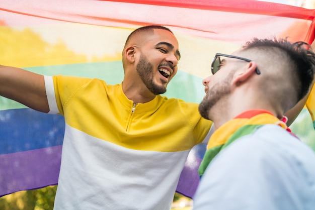 Homopaar die en hun liefde met regenboogvlag omhelzen tonen.