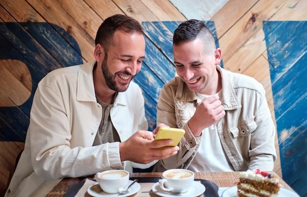 Homopaar lacht terwijl ze hun smartphone gebruiken in een coffeeshop
