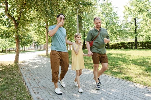 Homopaar wandelen met hun dochter in het park en ijs eten