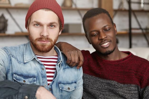 Homoseksualiteit, interraciale relaties, liefde en geluk concept. mannelijke partners van samesex brengen samen leuke tijd door in de coffeeshop, zitten dicht bij elkaar en praten over hun toekomst
