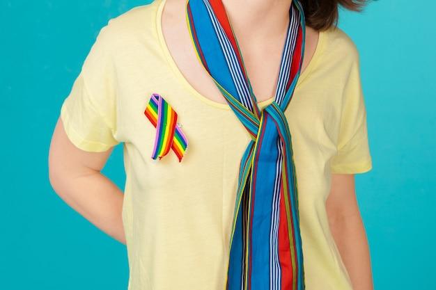 Homoseksueel en lgbt concept - sluit omhoog van vrouw die het vrolijke lint van de trotsvoorlichting op haar borst draagt