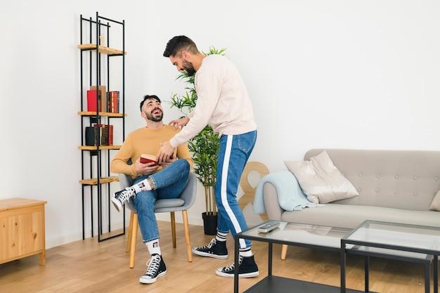 Homoseksueel jong homopaar die in de woonkamer genieten van