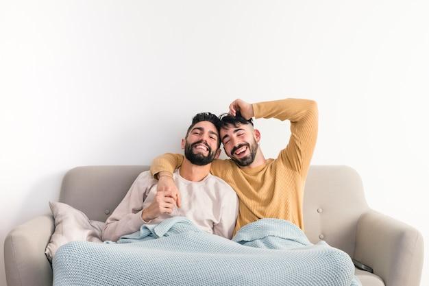 Homoseksueel jong vrolijk paar dat samen op bank tegen witte muur geniet van