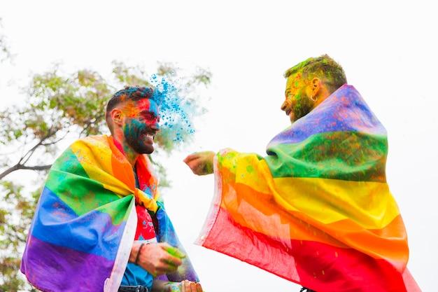 Homoseksuele mannen die elkaar besprenkelen met kleurrijk poeder