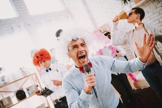 Homoseksuele mannen in kleurrijke kleding zingen karaoke op feestje.