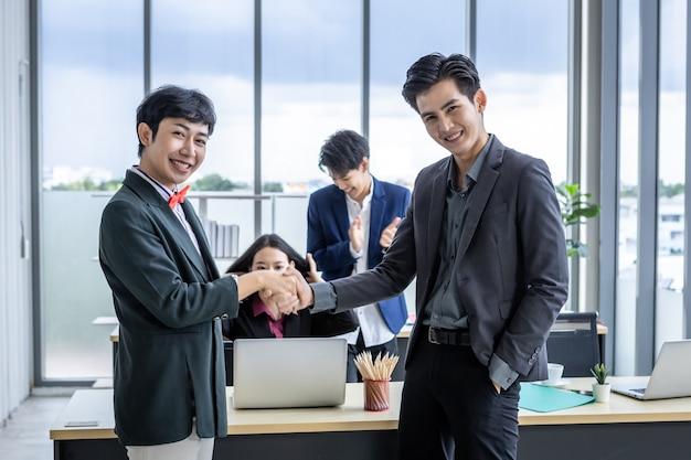 Homoseksuele zakenman lgbt-partners en zakenman die handen schudden op op de achtergrond van de kantoorruimte nadat het contract is ondertekend of de handdrukgroetovereenkomst, het bedrijf sprak vertrouwen aanmoedigen