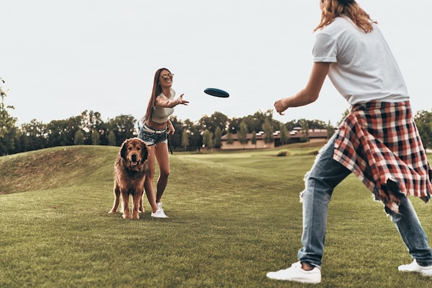 Hond brengt hen vreugde. volledige lengte van mooi jong stel dat plastic schijf gooit terwijl ze buiten met hun hond spelen