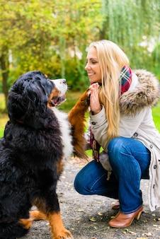 Hond die handen met poot schudt aan zijn vrouw