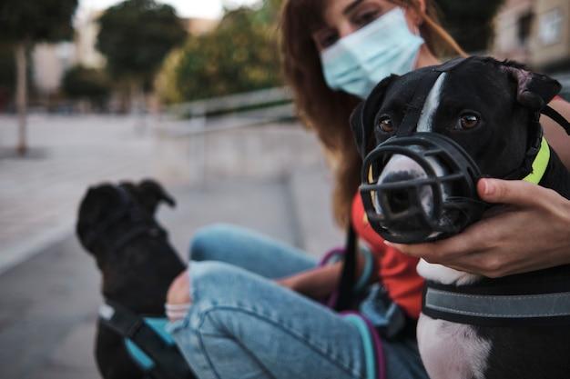 Hond die snuit draagt die wordt gestreeld door vrouwelijke eigenaar die een gezichtsmasker draagt. focus op de hond.