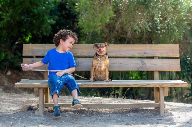 Hond en kind zittend op een houten bankje in het park. het kind kijkt naar zijn hond en lacht op een zonnige dag