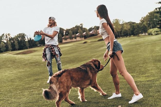 Hond houdt ze actief. volledige lengte van mooi jong stel dat plastic schijf gooit terwijl ze buiten met hun hond spelen