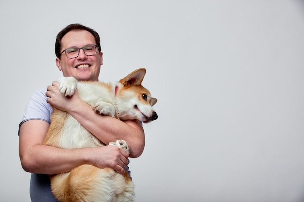 Hond ligt op de schouder van de eigenaar welsh corgi in de handen van zijn eigenaar op een witte achtergrond
