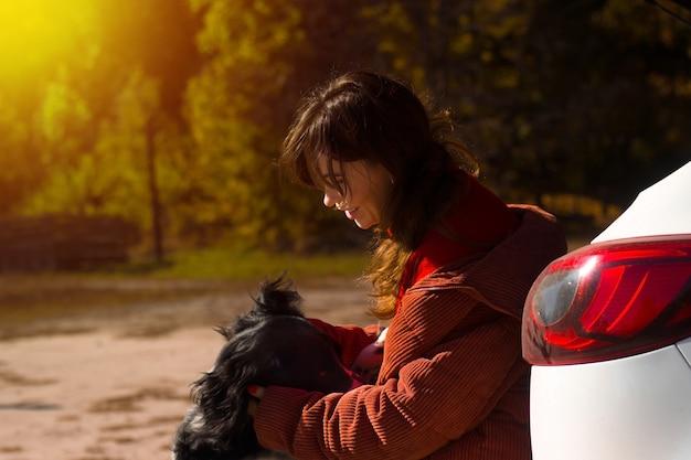 Hond russische spaniël leunt tegen de vrouwelijke meesteres bij de auto op straat