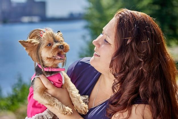 Hond yorkshire terrier in haar armen dikke volwassen blanke vrouw