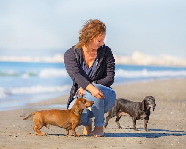 Honden en vrouw op het strand