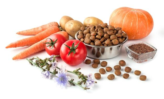 Honden- of kattenvoer op roestvrijstalen schaal met rauwe groenten op witte achtergrond voor ontwerp over dierenwinkel.