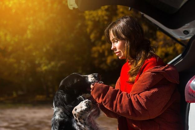 Hondenspaniël leunt tegen de vrouwelijke meesteres bij de kofferbak op straat