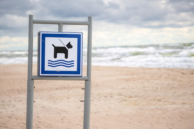 Hondenstrandbord met zand en brekende golven in de rug.