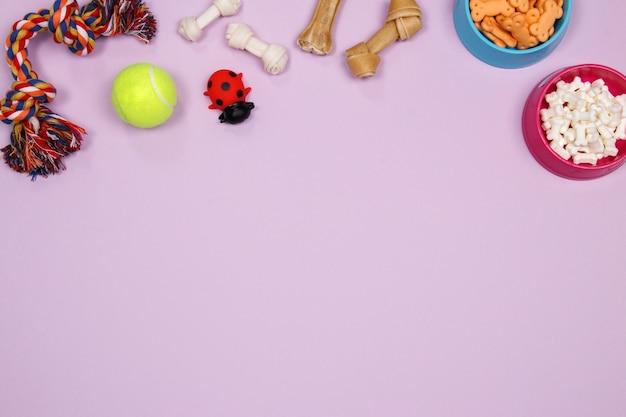 Hondentoebehoren, voedsel en stuk speelgoed op purpere achtergrond. plat leggen. bovenaanzicht.