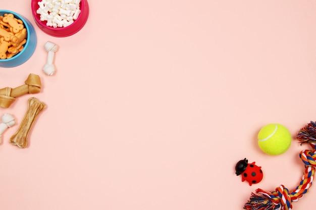Hondentoebehoren, voedsel en stuk speelgoed op roze achtergrond. plat leggen. bovenaanzicht.