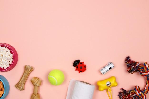 Hondentoebehoren, voedsel en stuk speelgoed op roze achtergrond.