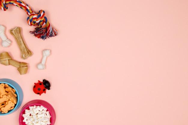 Hondentoebehoren, voedsel en stuk speelgoed op roze achtergrond