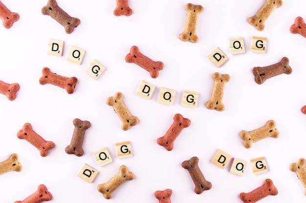 Hondenvoerpatroon gemaakt met droge snacks in de vorm van botten. woord hond in houten tegels. grappige plat lag textuur.