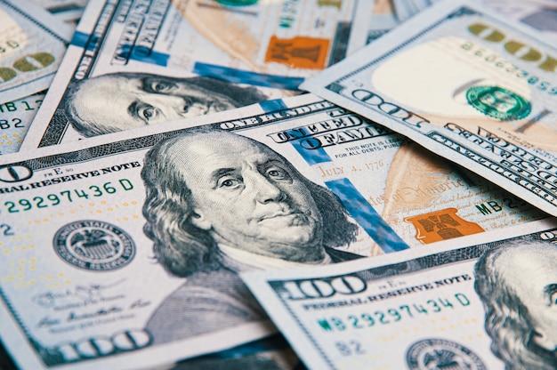 Honderd amerikaanse bankbiljetten zijn verspreid. contant honderd dollarbiljetten, dollar achtergrondafbeelding.
