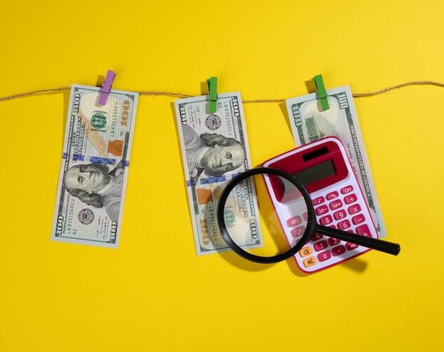 Honderd amerikaanse dollarbiljetten hangen aan een touw met wasknijpers, mag