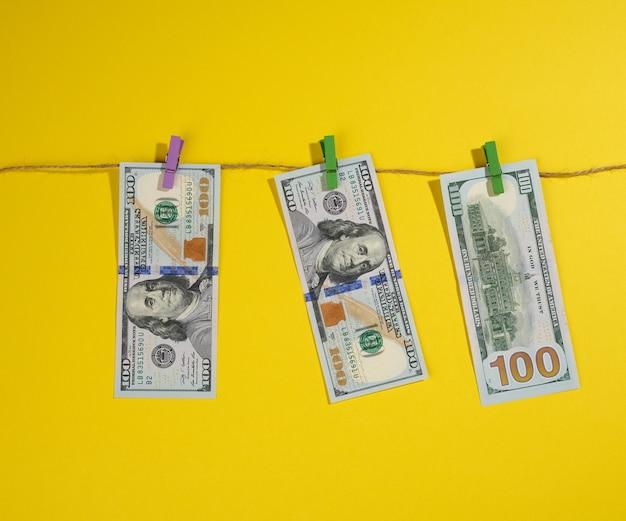 Honderd amerikaanse dollarbiljetten hangen aan een touw met wasknijpers, yel