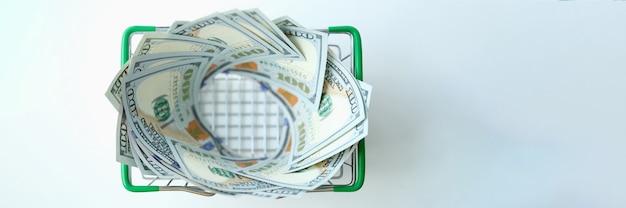 Honderd amerikaanse dollarbiljetten liggen in het winkelmandje