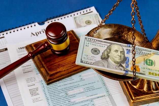 Honderd amerikaanse dollarbiljetten op een tafelweegschaal van gerechtigheid en hamer irs-formulier.