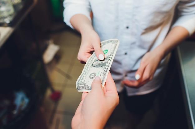 Honderd dollar in de hand van de vrouw.