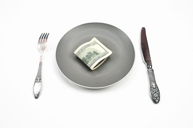 Honderd dollarbiljet op plaat, met vork en mes op geïsoleerde witte achtergrond. hoge kwaliteit foto