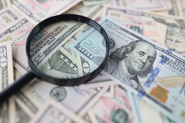 Honderd-dollarbiljetten en vergrootglas liggen op tafel op zoek naar een nieuw investeringsconcept