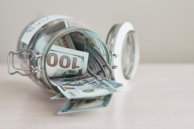 Honderd-dollarbiljetten in glazen pot met inscriptie opslaan op tafel. geld besparen en het concept van huisfinanciën