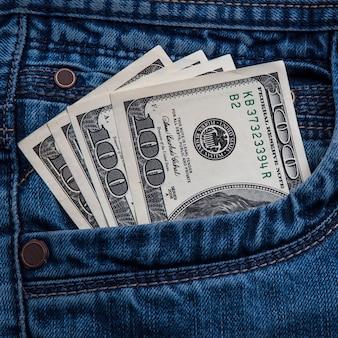 Honderd-dollarbiljetten steken uit je spijkerbroekzak.