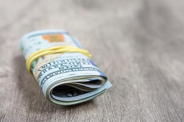 Honderd dollarsrekeningen die in een elastiekje over houten achtergrond worden ingepakt